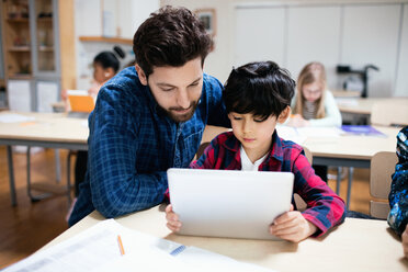 Teacher assisting male student in using digital tablet while sitting in classroom - MASF02759