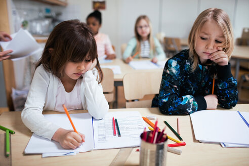 Students writing on paper at desk in classroom - MASF02762