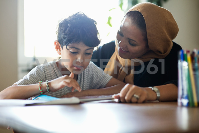 Smiling mother assisting son in using digital tablet while studying at home - MASF02765