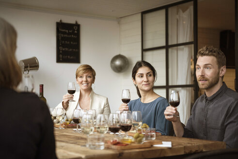 Smiling business people holding wineglass while sitting at table - MASF02807