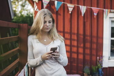 Teenage girl leaning on fence while text messaging against house in back yard - MASF02825