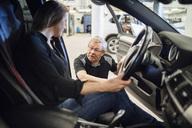 Senior expert discussing with female customer sitting in car at repair shop - MASF02831