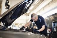 Senior mechanic holding mobile phone while repairing car at shop - MASF02834