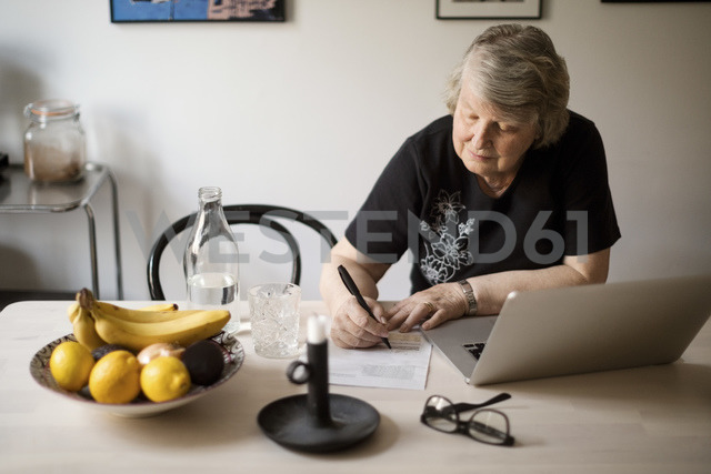 Senior woman checking for bills while using laptop at table - MASF02837