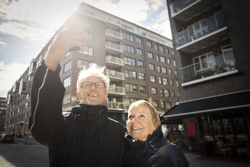 Senior couple taking selfie through smart phone while standing in city - MASF02840