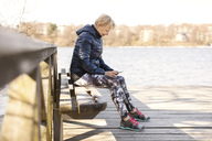 Senior woman in sportswear using phone while sitting on bench by lake - MASF02843