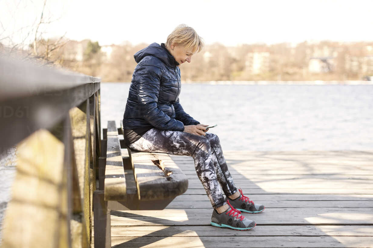 Senior woman in sportswear using phone while sitting on bench by lake - MASF02843 - Maskot ./Westend61
