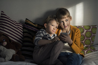 Siblings using mobile phone while sitting on sofa at home - MASF02858
