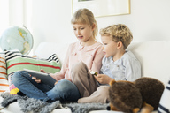 Siblings using digital tablet while sitting on sofa at home - MASF02864