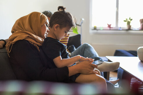 Side view of mother and son using digital tablet while sitting on sofa at home - MASF02867