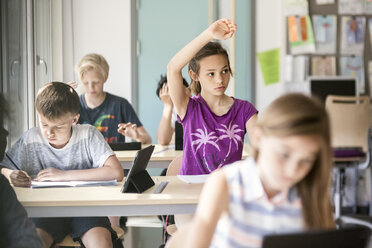 Schoolgirl raising hand at desk in classroom - MASF02873