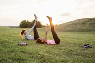 Side view of woman looking at daughter exercising on grass at park during sunset - MASF02876