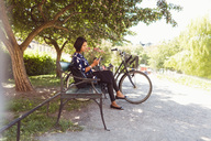 Side view of businesswoman using smart phone while sitting on park bench - MASF02879