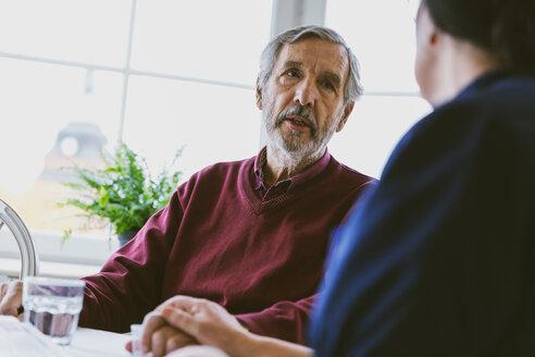 Senior man talking to female caretaker at home - MASF02885