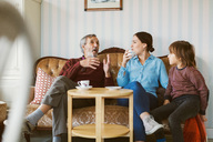 Senior man talking to daughter and great grandson on sofa in living room - MASF02894