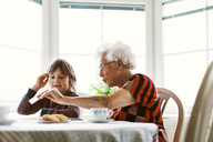 Senior woman showing card to great grandson at home - MASF02897