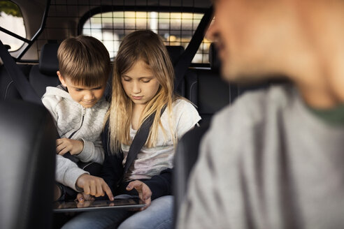 Sibling using digital tablet while sitting in car with father in foreground - MASF02903