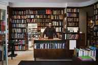 Portrait of owner standing against bookshelves in library - MASF02909