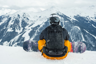 Rear view of man with snowboard sitting against snowcapped mountains - MASF02912