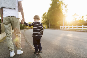 Rear view of boy walking with father while holding hands on street - MASF02918
