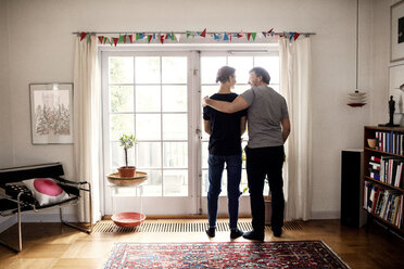 Rear view of father and son standing by door in new house - MASF02921