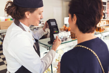 Saleswoman assisting female customer with credit card reader at grocery store - MASF02924