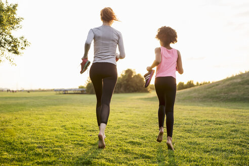 Rear view of woman and girl jogging while holding shoes on grass during sunset - MASF02930