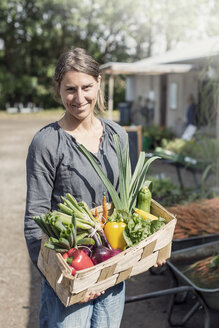 Portrait of happy woman carrying vegetables in basket - MASF02933