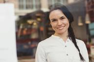 Portrait of smiling customer seen through glass window - MASF02936