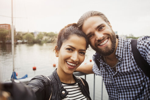 Portrait of smiling couple standing by river in city against clear sky - MASF02942