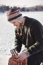 Young man putting thermos in bag while kneeling on snow covered field - MASF02945