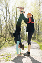 Woman helping sister doing handstand on road - MASF02957