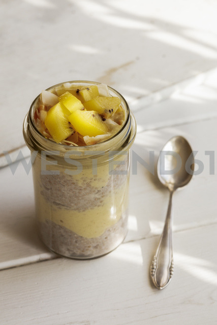 Glass of chia pudding with mango smoothie garnished with kiwi and coconut flakes - EVGF03358
