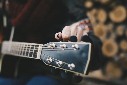 Young woman tuning guitar, close-up - OCAF00182