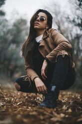 Cool young woman wearing sunglasses and leather jacket crouching on forest soil - OCAF00185