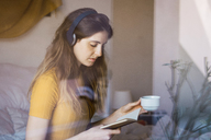 Young woman with coffee cup, headphones and notebook behind windowpane - KKAF00988