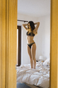 Young woman in underwear standing on bed with hands behind head - KKAF00994