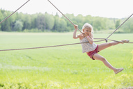 Portrait of girl hanging on rope over field during sunny day - MASF02964