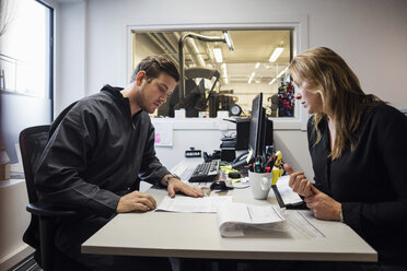 Owner and customer discussing over documents in auto repair shop - MASF02967
