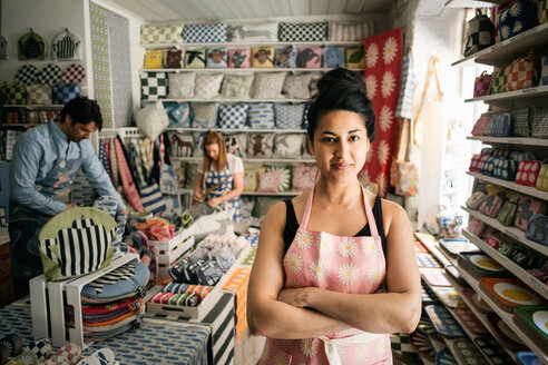 Portrait of confident owner standing with arms crossed while colleagues working in shop - MASF02970