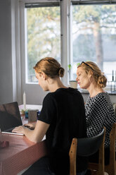 Mother and son using laptop at dining table by window - MASF02976