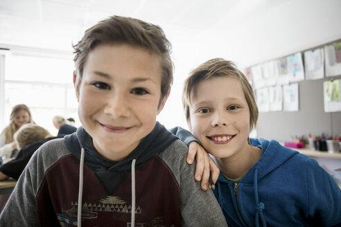 Portrait of happy schoolboys sitting in classroom - MASF02988