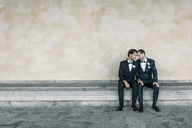 Newlywed gay couple sitting on bench against wall - MASF02991