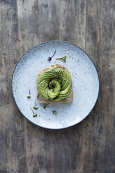 Open sandwich with sliced avocado in plate on wooden table - MASF02994