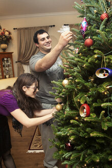 Couple decorating Christmas tree at home - CAVF36263