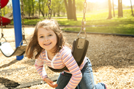 Portrait of happy girl swinging in playground - CAVF36278
