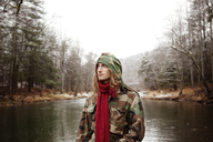 Man looking away while standing against lake during winter - CAVF36305