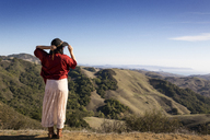 Rear view of woman standing on mountain and looking at view - CAVF36374