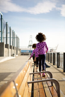 Rear view of girls walking on wooden bench at promenade against sky - CAVF36458