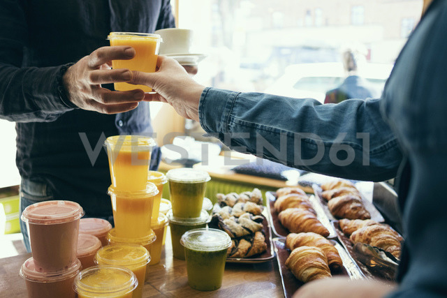 Midsection of owner serving juice to male customer in coffee shop - MASF03010